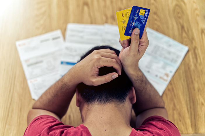 Top view of stressed young Asian man holding credit cards and thinking about finding money to pay credit card debt and all bills. He is holding head by another hand. Financial problem concept.