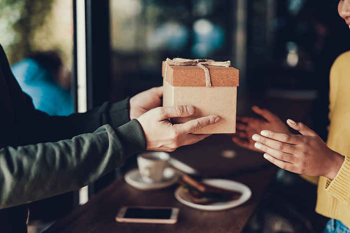 Sweet moments concept. Cropped photo hands with gift. Man sharing present to her woman. They standing inside cafe