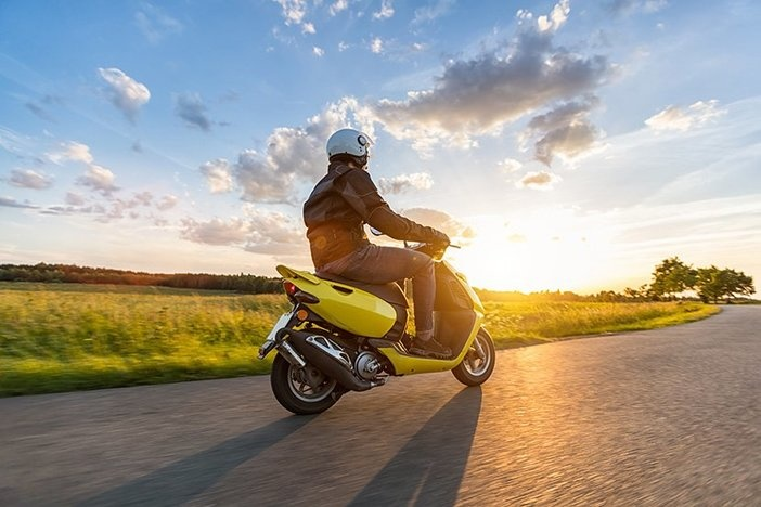 Motorbiker riding on empty road with sunset light, concept of speed and touring in nature. Small motorcycle scooter