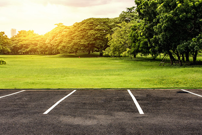 parking lot butting up against vacant land