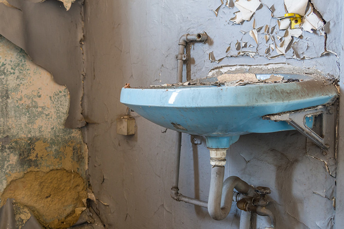 old blue bathroom sink with exposed pipes in trashed bathroom with peeling gray walls and holes in the wall