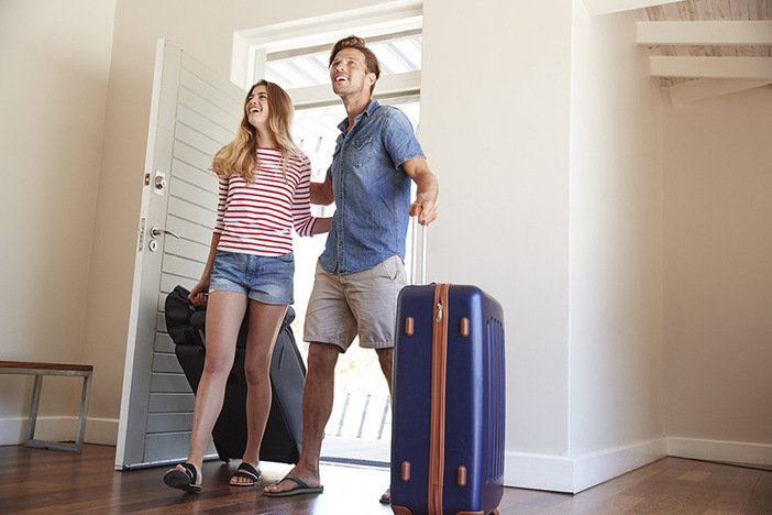 couple walking in front door of vacation rental with suitcases